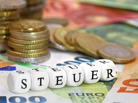 german word for Tax, STEUER, written with letter cubes on euro banknotes and coins background, concept image of increasing tax or paying taxes Archivio Fotografico