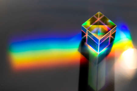 Colored square crystal with a rainbow on a substrate in close-up Stock Photo