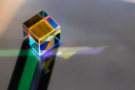 Colored square crystal with a rainbow on a substrate in close-up
