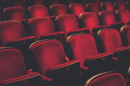 desaturated colors: Empty comfortable red seats with numbers in cinema Stock Photo