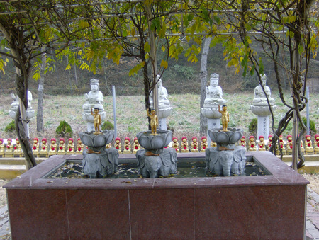 sanctification: small statues of the Buddha standing in the bowl of lilies on the backs of elephants.