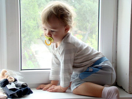 considering: the child on the windowsill,considering a toy