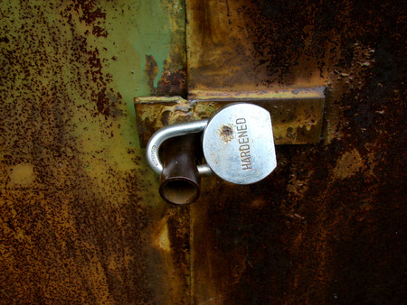 hardened: closed lock,hardened on a rusty gate.