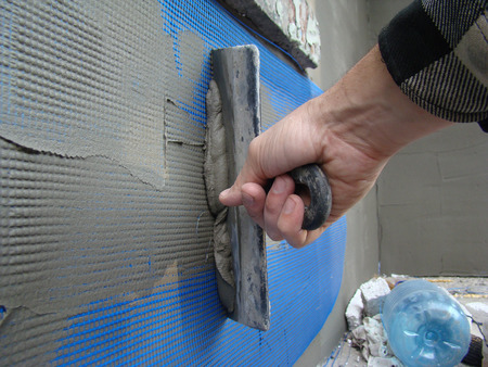 reinforcing: puttying reinforcing mesh putty for exterior works with the spatula
