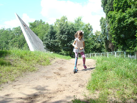 pamper: a child riding a scooter down the hill