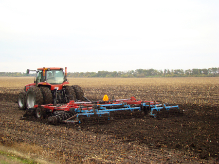 tractor plowing the field after harvest in autumn Фото со стока