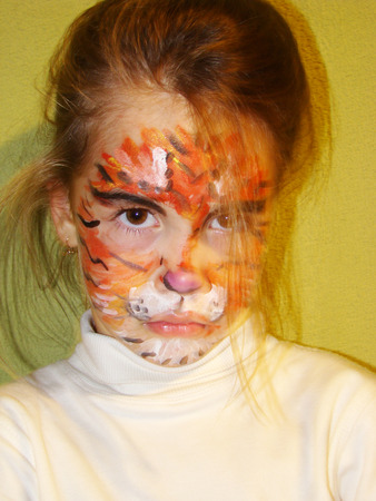 baby facial expressions: a beautiful little girl with painted face like a tiger Stock Photo