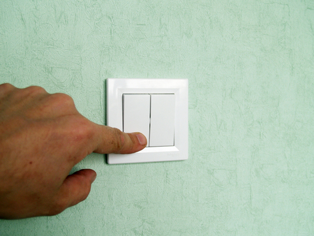 hand turns off the light on the switch located on the wall Standard-Bild - 116640506