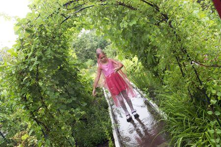 child in the rain in a raincoat Standard-Bild - 131913556