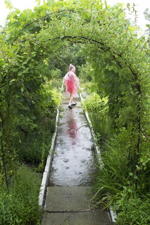 child in the rain in a raincoat Standard-Bild - 131913696