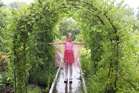 child in the rain in a raincoat Standard-Bild - 131915124