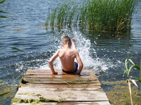 child swimming in the river climbs to the surface of the pier Standard-Bild - 136744596