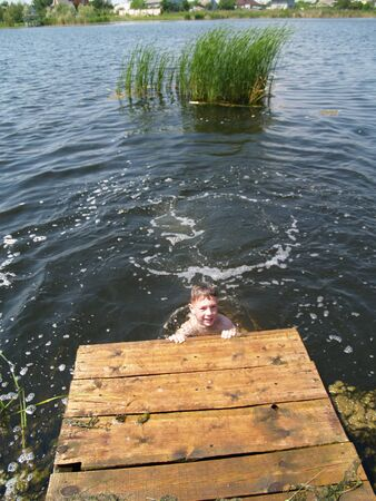 child swimming in the river climbs to the surface of the pier Standard-Bild - 136744602