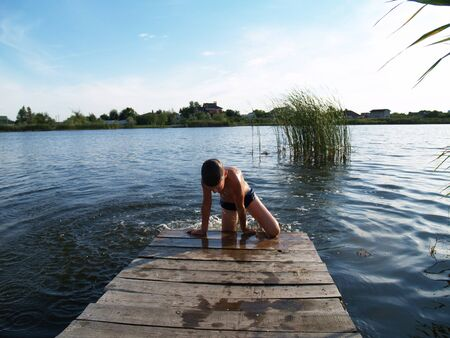 child swimming in the river climbs to the surface of the pier Standard-Bild - 136744606