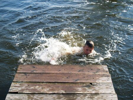 child swimming in the river climbs to the surface of the pier Standard-Bild - 136744610