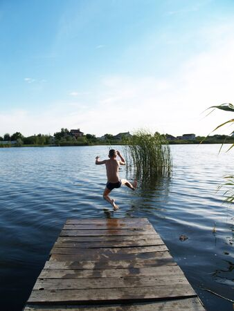 child swimming in the river climbs to the surface of the pier Standard-Bild - 136744611