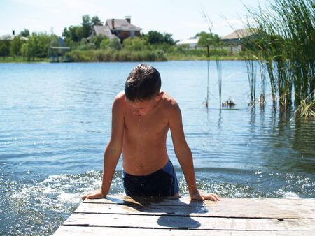 child swimming in the river climbs to the surface of the pier Standard-Bild - 136744909