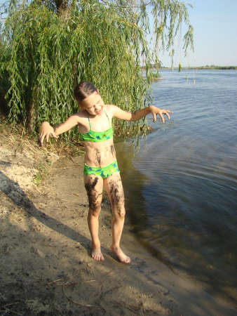 child puts river mud on his body on the river Bank