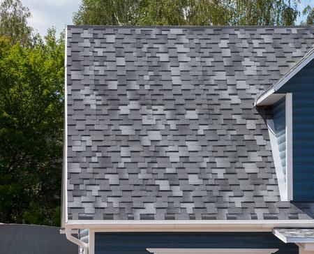 tejas: El techo de la casa forrada con tejas de asfalto gris Foto de archivo