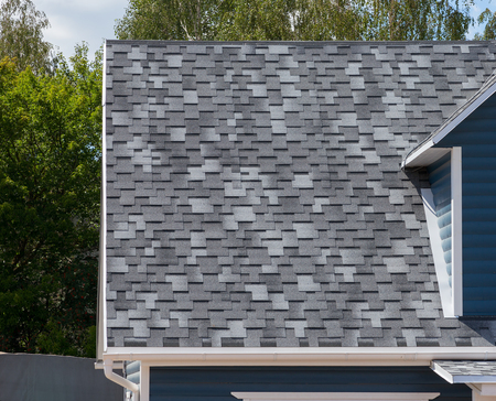 bitumen: The roof of the house lined with gray bitumen shingles Stock Photo
