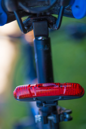 Rear red bicycle lamp installed at the seatpost Stock Photo