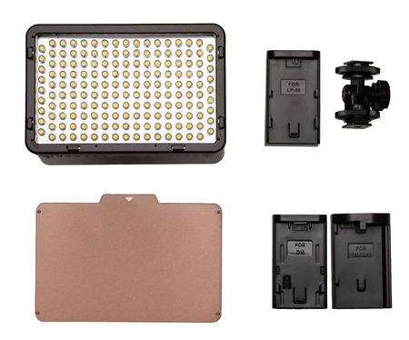 adapters: On-camera LED video light kit flat lay. Video Light, tungsten filter, mounting thread, adapters for battery. On white background.