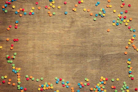 Party frame or border of colorful confetti arranged on a rustic old brown wooden background Stock Photo