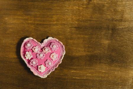 trabajo manual: corazón rosado del trabajo hecho a mano con un patrón se encuentra en un fondo de madera. Un fondo para el Día de San Valentín. Lugar para el texto