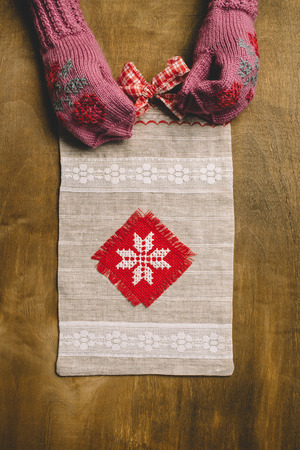 trabajo manual: Gift package of handwork with a bow and red ornament on a wooden background