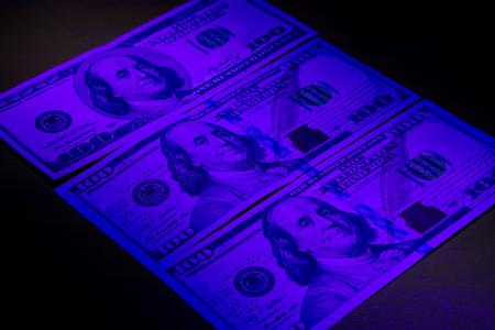 ultraviolet: Three hundred dollar bills under ultraviolet light. Stock Photo