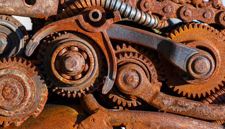 sprockets: Part of the old mechanism with metal gears, sprockets, chain and other parts covered with rust.