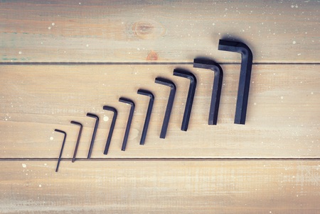 Old hex keys are laid out from the smaller to the larger on a wooden background Stok Fotoğraf