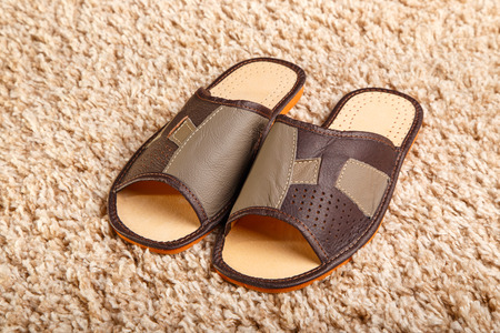Mens leather slippers stand on a mat