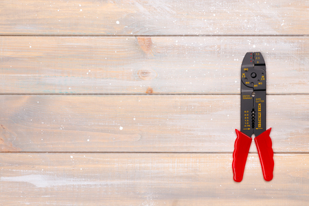 cable cutter: Wire stripper lies on the wooden background. Place for the text.
