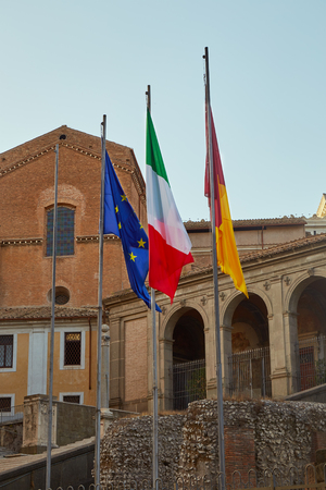 Flags of the European Union, Italy and Rome weigh on flagpoles near the Roman Forum