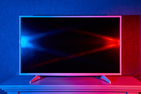 A modern flat LED TV on a stand is lit in red and blue colors  Stock Photo