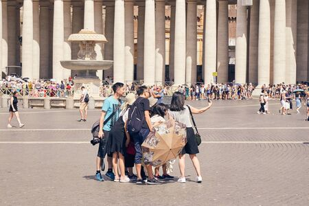 ROME - AUGUST 3: A group of Asian tourists do selfie in the Vatican area next to St. Peters Cathedral August 3, 2017 in Rome, Italy Editorial
