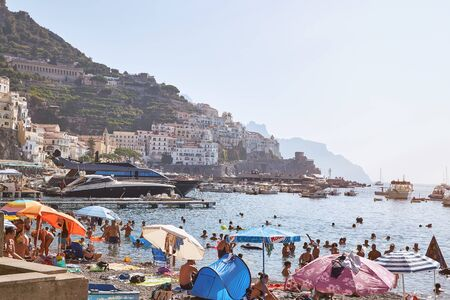 Amalfi, Italy - August 09, 2017: Panorama of the city of Amalfi with beach, parasols, boats, sea and city view, Italy