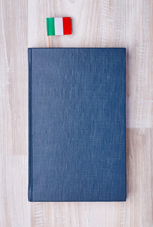 Flat lay of blue textured notepad with Italian flag on toothpick as bookmark.