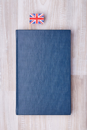 Flat lay of blue textured notepad with British flag on toothpick as bookmark.