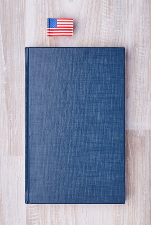 Flat lay of blue textured notepad with American flag on toothpick as bookmark.