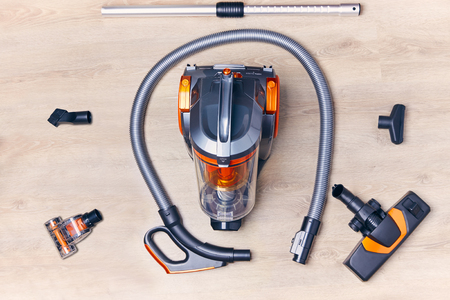 Top view of a modern vacuum cleaner with a container with nozzles and a hose spread out around it