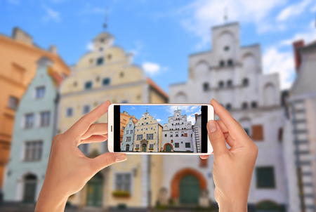A tourist is taking a photo of building complex of old buildings - The Three Brothers - Riga, Latvia on a mobile phone Banque d'images