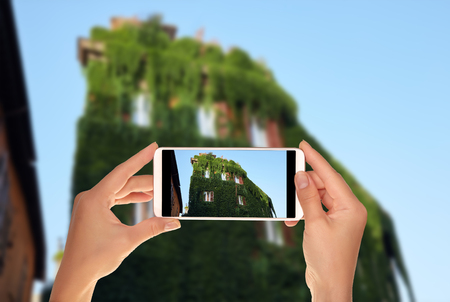 A tourist is taking a photo of the building is completely overgrown with vine lightly in Trastevere district, Rome, Italy on a mobile phone