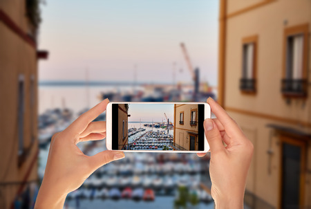 A tourist is taking a photo of a sea dock for small motor boats and cutters with a port in the background in the Italian city of Salerno on a mobile phone