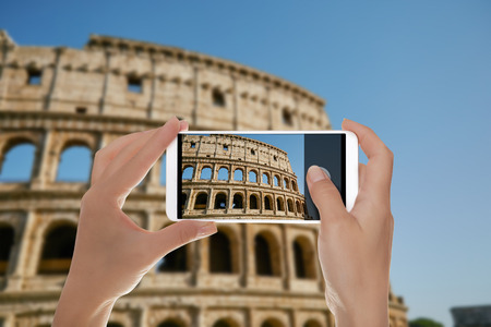 A tourist is making a photo of the Coliseum against the blue sky Rome, Italy on a mobile phone