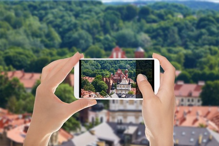 A man is making a photo of panorama of Vilnius with a view of the Church of the Saint Francis Assisi on a mobile phone