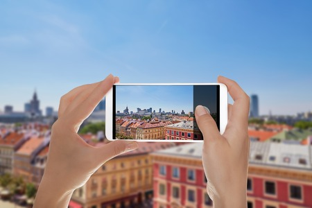 A man is making a photo of view from above of the Poland capital - Warsaw in summer day on a mobile phone Banque d'images