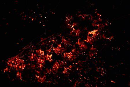 Abstraktes Foto von glühenden roten Kohlen auf dunklem Hintergrund