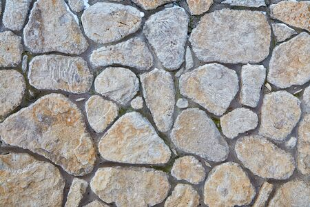 Grey stone wall with interesting texture of stones. Vintage background of grey wall. Stock Photo